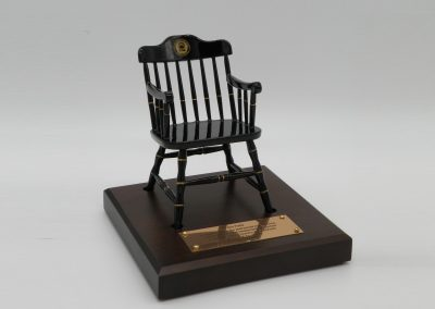 black captain's chair on brown maple base with brass plate